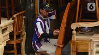 Pekerja melakukan proses finishing pembuatan furnitur atau perlengkapan rumah berbahan kayu khas Jepara di Ciputat, Tangerang Selatan, Selasa (14/9/2021). Pedagang di tempat tersebut mengakui selama PPKM ini daya beli masyarakat terhadap furnitur meningkat. (Liputan6.com/Johan Tallo)
