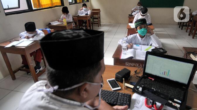 Guru saat mengajar di SDN Pondok Labu 14 Pagi di Cilandak, Jakarta Selatan, Jumat (4/6/2021). Kegiatan belajar tatap muka masih masih menerapkan pola 50 persen siswa belajar di rumah secara online untuk setiap kelas mengantisipasi penyebaran virus covid-19. (merdeka.com/Arie Basuki)