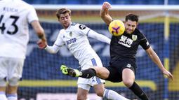 Striker Leeds United, Patrick Bamford, berebut bola dengan pemain Burnley, James Tarkowski, pada laga Liga Inggris di Stadion Elland Road, Minggu (27/12/2020). Leeds United menang dengan skor 1-0. (Oli Scarff/Pool via AP)