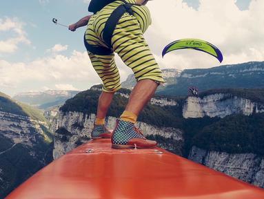 Seorang pria berada di atas papan selancar saat melintas di atas tali yang diikat diantara dua tebing di Perancis, Rabu (9/11). Olahraga Flying Frenchies adalah salah satu olahraga ekstreem. (REUTERS/ redbullcontentpool)