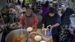 Sukarelawan memindahkan makanan ke dalam kotak di Masjid Bang Aw, Bangkok, Thailand, Kamis (30/4/2020). Setiap hari selama Ramadan, sukarelawan membagikan makanan kepada 150 keluarga sekitar Masjid Bang Aw yang tidak bisa beribadah bersama karena pandemi COVID-19. (AP Photo/Gemunu Amarasinghe)