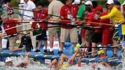 Para pelatih menyodorkan botol minuman kepada perenang yang sedang berlaga dalam lomba renang air terbuka nomor 10 km putra di Kejuaraan Renang Dunia di Yeosu, Korea Selatan, Selasa (16/7/2019). (AP Photo/Mark Schiefelbein)