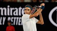 Petenis Swiss, Roger Federer mengembalikan bola ke arah Taylor Fritz dari AS dalam babak 32 besar Australia Terbuka di Melbourne, Jumat (18/1). Federer melaju mulus ke babak 16 besar setelah menang tiga set langsung 6-2 7-5 6-2. (DAVID GRAY/AFP)