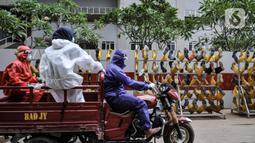 Rizky (33) bersama rekan Tim Sterilisasi menggunakan sepeda motor saat mengangkut sepatu tenaga kesehatan yang bertugas menangani pasien Covid-19 untuk dicuci di Rumah Sakit Darurat (RSD) Wisma Atlet Kemayoran, Jakarta. (merdeka.com/Iqbal Nugroho)