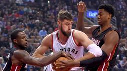 Pemain Toronto Raptors, Jonas Valanciunas (tengah) dihadang pemain Miami Heatpada laga NBA di Air Canada Centre, (4/11/2016). Raptors menang 96-87. (Reuters/Dan Hamilton-USA TODAY Sports)
