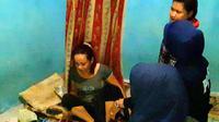 Ketiga emak-emak itu asyik berjudi dengan membanting kartu joker saat tawa mereka mendadak terhenti. (Liputan6.com/Ahmad Akbar Fua)