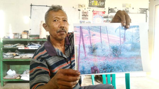 Direktur LSM Setam, Petrus Sugeng memperlihatkan foto tanah yang disengketakan antara warga Wanareja dengan Perhutani. (Foto: Liputan6.com/Muhamad Ridlo).