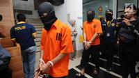Tersangka kasus penyebaran ujaran bernada kebencian lewat internet digiring polisi usai rilis di Jakarta, Rabu (23/8). Tiga tersangka masuk dalam satu kelompok. (Liputan6.com/Helmi Fithriansyah)