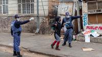 Sejumlah polisi membujuk seorang warga untuk pulang ke rumah di Johannesburg, Afrika Selatan, Senin (30/3/2020). Presiden Afrika Selatan Cyril Ramaphosa menetapkan karantina wilayah atau lockdown nasional selama 21 hari untuk mencegah penularan virus corona COVID-19. (Xinhua/Yeshiel Panchia)