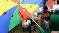 Pengungsi korban gempa dan tsunami Palu menuang air di tenda pengungsian lapanga Walikota Palu, Sulteng, Senin (8/10). Pemerintah akan membangun barak pengungsian bagi korban gempa dan tsunami di Kota Palu, Sigi dan Donggala. (Liputan6.com/Fery Pradolo)