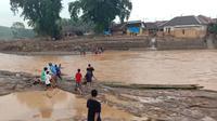 Evakuasi hanya mengandalkan perahu karet yang diikat ke sebuah tali, lalu ditarik oleh warga di tengah derasnya aliran Sungai Ciberang, di Kecamatan Sajira, Kabupaten Lebak, Banten. (Liputan6.com/ Yandhi Deslatama)