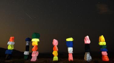 """Meteor Perseid melintasi langit di atas instalasi seni """"Seven Magic Mountains"""" dekat Jean, Nevada (13/8). Puncak hujan meteor perseid terjadi pada 11-12 Agustus dan 12-13 Agustus. (AFP Photo/Ethan Miller)"""