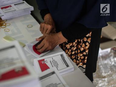 Seorang pekerja menyelesaikan pelipatan surat suara Pemilihan Umum 2019 di gudang logistik KPU Jakarta Pusat, Selasa (19/2). Proses pelipatan surat suara diiikuti 62 orang yang direkrut dari wilayah sekitar gudang KPU.(Www.sulawesita.com)