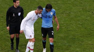 Penyerang Portugal, Cristiano Ronaldo membantu Edinson Cavani yang Cedera keluar lapangan saat pertandingan babak 16 besar Piala Dunia 2018 di Stadion Fisht di Sochi, Rusia (30/6). Cavani cedera kisaran menit ke 70. (AP Photo/Darko Vojinovic)