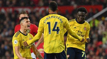 Para pemain Arsenal merayakan gol yang dicetak Pierre-Emerick Aubameyang ke gawang Manchester United pada laga Premier League di Stadion Old Trafford, Manchester, Senin (30/9). Kedua klub bermain imbang 1-1. (AFP/Paul Ellis)