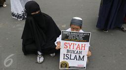 Seorang anak memegang poster saat mengikuti aksi Tarhib Ramadhan di Bundaran HI, Jakarta Pusat, Minggu (29/5). Aksi tersebut selain Tarhib Ramadhan mereka juga menolak ajaran syi'ah, Komunis dan kaum LGBT. (Liputan6.com/Herma Zakharia)