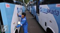 Petugas membersihkan Kopaja terintegrasi Transjakarta terparkir di Parkir Timur Senayan, Jakarta, Selasa (22/12). Saat ini terdapat 320 bus tampilan baru Kopaja AC yang akan beroperasi di rute-rute yang terintegrasi.  (Liputan6.com/Johan Tallo)