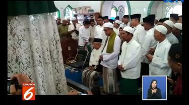 Ma'ruf tampak duduk di depan jemaah lain yang duduk bersila mengelilingi sekitar makam.