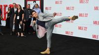 Bintang laga, Iko Uwais memamerkan gerakan pencak silat ketika menghadiri acara gala premier film Mile 22 di Los Angeles, Kamis (9/8). Iko Uwais tampil dalam balutan setelan jas abu-abu yang dipadukan dengan kaus warna gelap. (Jordan Strauss/Invision/AP)