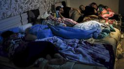 Warga menonton TV Negara saat berkumpul dalam tempat penampungan untuk melindungi diri dari serangan bom di Stepanakert, Republik Nagorno-Karabakh, Azerbaijan, 28 September 2020. Serangan antara Armenia dan Azerbaijan menewaskan puluhan orang. (Armenian Foreign Ministry via AP)