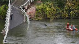 Tim penyelamat menyelam di  sungai Tarm, dekat jembatan gantung yang ambruk di Prancis, Selasa (18/11/2019). Sebanyak 60 petugas penyelamatan, 40 anggota kepolisian, 67 petugas pemadam kebakaran, dan beberapa penyelam dikerahkan untuk melakukan pencarian di dalam sungai Tarn. (ERIC CABANIS/AFP)