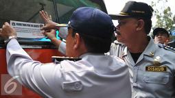 Petugas Dishub menempelkan stiker saat menggelar operasi uji kelengkapan surat kendaraan angkutan umum di Terminal Pasar Minggu, Senin (26/10/2015). Kegiatan ini untuk meningkatkan kapasitas pelayanan terhadap angkutan umum. (Liputan6.com/Gempur M Surya)