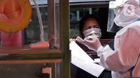 Petugas berpakaian APD lengkap melayani pasien yang secara mandiri melakukan swab test drive thru di halaman parkir rumah sakit di Jakarta, Rabu (12/5/2020). Swab test drive thru dilakukan untuk mendeteksi dan mencegah penyebaran virus corona COVID-19. (Liputan6.com/Johan Tallo)