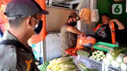 Pelanggar PSBB mengenakan rompi khusus saat razia masker di Pasar Reni, Pamulang, Tangerang Selatan, Banten, Selasa (1/9/2020). Razia terhadap pedagang dan pengunjung pasar ini juga dilakukan rapid test guna mencegah penularan COVID-19. (merdeka.com/Arie Basuki)