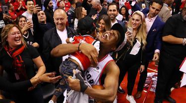 Pebasket Toronto Raptors, Kyle Lowry, menggendong putranya usai mengalahkan Milwaukee Bucks pada NBA Final Wilayah Timur di Scotiabank Arena, Toronto, Sabtu (25/5). Raptors menang 4-2 atas Bucks. (AFP/Gregory Shamus)