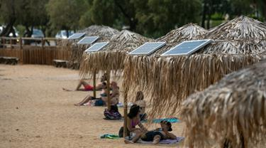 Panel surya terpasang pada sejumlah payung di pantai dekat Balai Kota Vari-Voula-Vouliagmeni, Yunani, Selasa (21/7/2020). Puluhan payung di sepanjang pantai tersebut dilengkapi sistem panel surya dan port USB untuk menyediakan pengisian daya gratis dan ramah lingkungan. (Xinhua/Lefteris Partsalis)