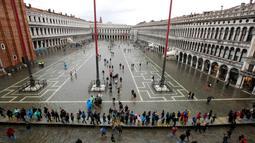 Warga berjalan di Alun-Alun Santo Markus yang banjir akibat terjangan gelombang pasang di Venesia, Italia, Selasa (12/11/2019). Venesia dilanda banjir akibat gelombang pasang setinggi 127 cm. (AP Photo/Luca Bruno)