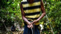 Abdul Samad Ahmad mengikat tali sebelum mengambil madu di hutan Ulu Muda di Sik, Malaysia (11/3). Pada malam hari di hutan Malaysia, dua pemburu madu berada di dahan pohon menggunakan obor untuk menarik ribuan lebah. (AFP Photo/Manan Vatsyayana)