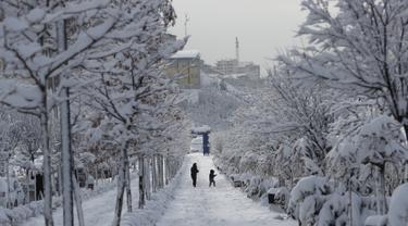 Seorang wanita dan anak berjalan di sepanjang trotoar salju di tengah-tengah pohon yang tertutup salju setelah salju yang turun di malam hari di Ankara, Turki (26/12). (AFP Photo/Adem Altan)