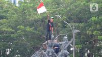 Massa aksi demo tolak omnibus law UU Cipta Kerja naik ke atas patung arjuna wiwaha mengibarkan bendera merah putih di Jalan Medan Merdeka Barat, Jakarta Pusat, Selasa (20/10/2020). (merdeka.com/ Arie Basuki)