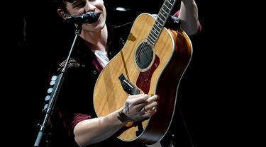 Shawn Mendes memang selalu identik dengan gitar akustik miliknya. (Liputan6.com/AFP)