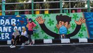 Warga berpose dengan mural yang mengajak orang untuk memakai masker di tengah pandemi Covid-19 di Surabaya, Jawa Timur, Minggu (25/10/2020). Mural di sepanjang dinding itu sebagai sarana imbauan kepada masyarakat untuk menerapkan protokol kesehatan pencegahan penularan COVID-19. (Juni Kriswanto/AFP)