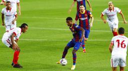 Striker Barcelona, Ansu Fati, berusaha melewati pemain Sevilla pada laga Liga Spanyol di Stadion Camp Nou, Minggu (4/10/2020). Kedua tim bermain imbang 1-1. (AP Photo/Joan Monfort)