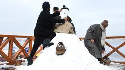 Sejumlah pria Kashmir membuat boneka salju di tepi Danau Dal setelah salju turun di Srinagar, India bagian utara, Sabtu (5/1). Wilayah Kashmir mengalami salju selama beberapa hari yang mengakibatkan terputus jalan raya Jammu-Srinagar (TAUSEEF MUSTAFA/AFP)