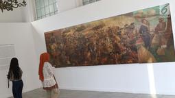Pengunjung lukisan Penyerangan Pasukan Mataram ke Batavia karya S.Sudjojono yang dipamerkan pada pameran seni rupa koleksi nasional #2 yang bertema Lini Transisi di Galeri Nasional, Jakarta, Selasa (13/8/2019). Pameran berlangsung hingga 31 Agustus mendatang. (Liputan6.com/Helmi Fithriansyah)