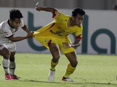 Gelandang Madura United, Andik Vermansah menarik baju bek Bhayangkara FC, Nurhidayat, pada laga Liga 1 2019 di Stadion Madya, Jakarta, Senin (5/8). (Bola.com/M iqbal Ichsan)