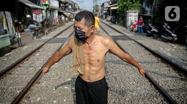 Seorang pria berjemur di bantaran rel di kawasan pemukiman padat Pejompongan, Jakarta, Selasa (6/7/2021). Berjemur diri di bawah matahari di antara pukul 08.00-11.00 WIB merupakan salah satu upaya yang paling sederhana untuk menjaga kesehatan selama wabah virus COVID-19. (Liputan6.com/Faizal Fanani)