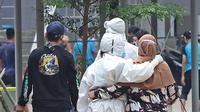 Tenaga kesehatan mendampingi pasien berstatus OTG (Orang Tanpa Gejala) yang tiba di RSDC Wisma Atlet, Jakarta, Selasa (26/1/2021). Hari ini, Selasa (26/1) kasus COVID-19 di Indonesia bertambah 13.094 sehingga total menyentuh angka satu juta, tepatnya 1.012.350. (Liputan6.com/Herman Zakharia)