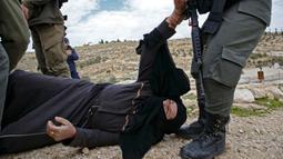 Polisi Israel membangunkan seorang perempuan Palestina yang terjatuh saat memprotes pembongkaran rumah di Desa Al-Dirat, dekat kota Hebron, Tepi Barat (16/1/2020). Pembongkaran itu menurut otoritas Israel dilakukan karena rumah dibangun tanpa izin. (AFP/Hazem Bader)