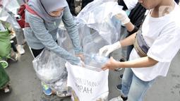 Aktivis Sekolah Relawan memilah sampah plastik saat aksi Jakarta Clean Action selama HBKB di Bundaran HI, Jakarta, Minggu (1/12/2019). Aksi digelar dalam rangka mengedukasi masyarakat agar peduli membuang sampah pada tempatnya guna menjadikan Jakarta kota bebas sampah. (merdeka.com/Iqbal S. Nugroho)