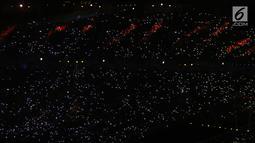 Ribuan penonton menyalakan flash ligt di ponselnya masing-masing saat malam penutupan Asian Games 2018 di Stadion GBK, Jakarta, Minggu (9/2). Hal ini menjadi unik dan menambah syahdu malam penutupan Asian Games 2018. (Liputan6.com/Helmi Fithriansyah)