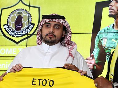 Penyerang asal Kamerun Samuel Eto'o berpose dengan jersey klub barunya  Qatar Sports Club selama presentasi dirinya di Doha, (14/8). Eks Striker Barcelona ini menandatangani kontrak selama satu tahun di klub tersebut. (AFP Photo/Karim Jaafar)
