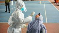 Petugas medis melakukan tes usap atau swab kepada warga di Pekanbaru untuk mendeteksi Covid-19. (Liputan6.com/M Syukur)