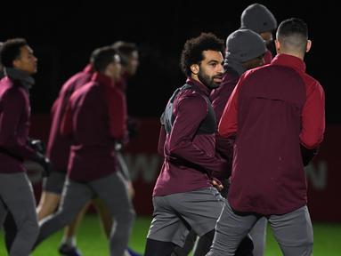Mohamed Salah mulai berlatih dengan rekan setim jelang laga lanjutan Liga Champions melawan Napoli yang berlangsung di stadion Anfiled, Inggris, Rabu (13/12). Liverpool membutuhkan kemenangan agar bisa lolos ke babak gugur. (AFP/Paul Ellis)