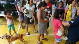 Para warga membawa hewan piaraannya untuk diberi vaksin anti rabies di Payatas, Manila, Filipina, Selasa (26/9). Menjelang Hari Rabies Sedunia, HSI pelopori kampanye anti-rabies untuk mencapai berantas infeksi rabies pada 2020. (AP Photo/Bullit Marquez)