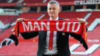 Ole Gunnar Solskjaer menunjukkan syal Manchester United saat konferensi pers di Stadion Old Trafford, Inggris, (28/3). Pria asal Norwegia tersebut mulai duduk di kursi manajer MU pada 19 Desember 2018, menggantikan peran Jose Mourinho. (AP Photo/Rui Vieira)